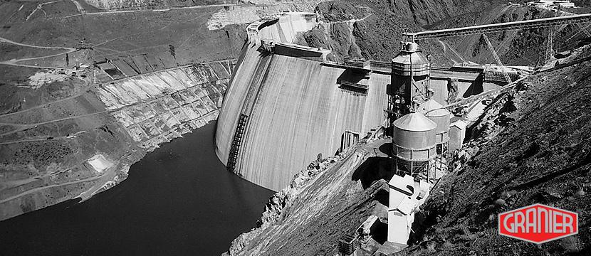 Foto antigua de una planta de hormigón de torre, junto a una presa